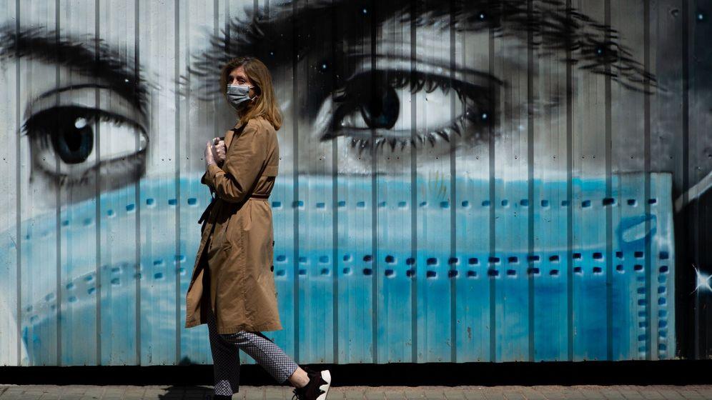 Foto: Una mujer camina ante un grafiti en Barcelona esta semana.