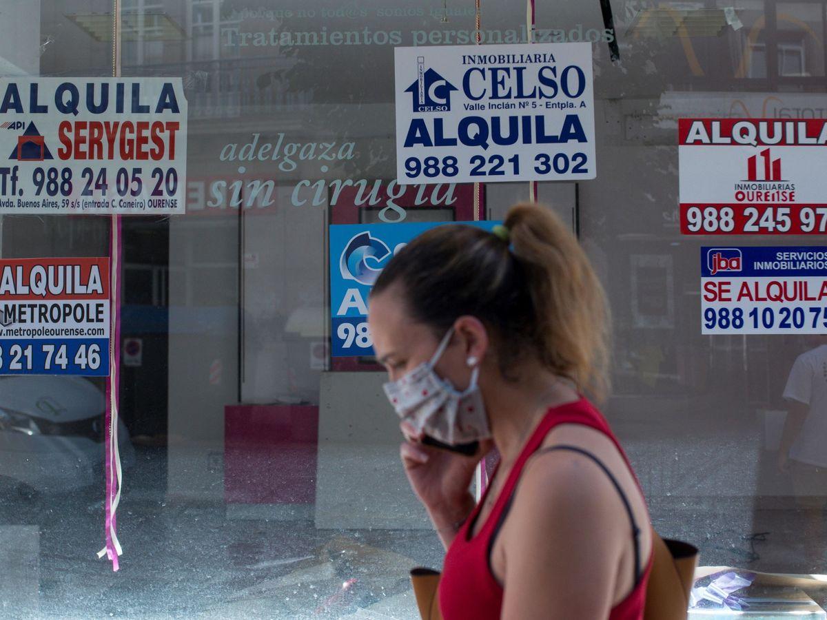 Foto: Una mujer pasa ante un comercio cerrado que se alquila. (EFE)