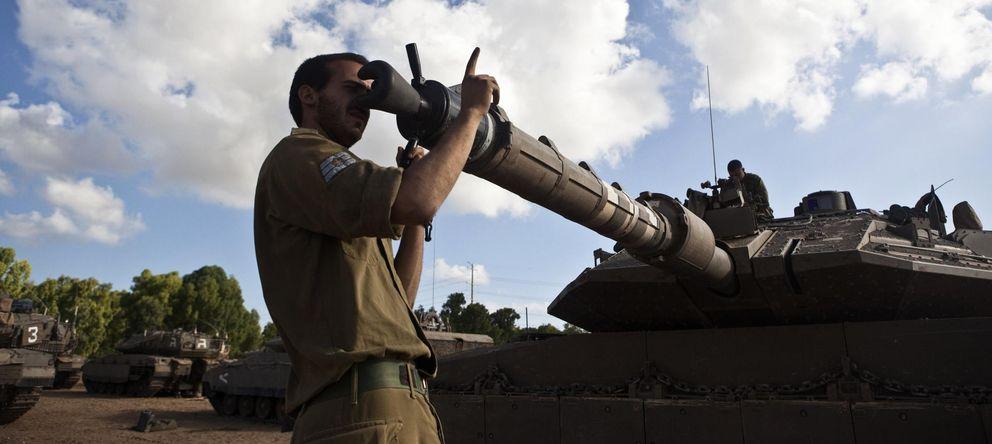 Foto: Un soldado israelí comprueba el cañón de un tanque en un puesto militar instalado en las frontera con la Franja de Gaza. (Reuters)