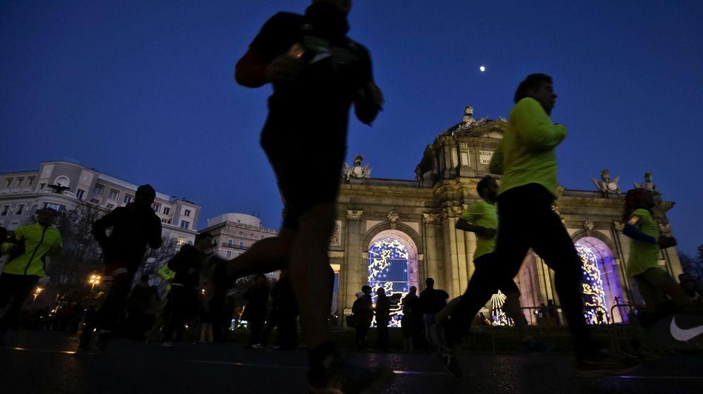 Foto: Varias personas pasan por la Puerta de Alcalá de Madrid durante la San Silvestre Popular (Efe/Emilio Naranjo)