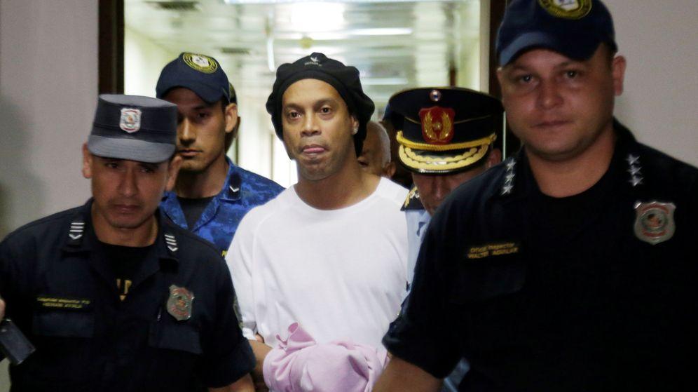 Foto: Ronaldinho, esposado y escoltado por la policía al interior de su celda en Paraguay. (Reuters)