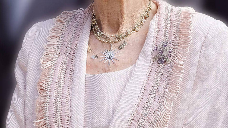 Detalle del colgante de la reina Sofía, con las iniciales de sus hijos y nietos en pequeñas medallas. (EFE)