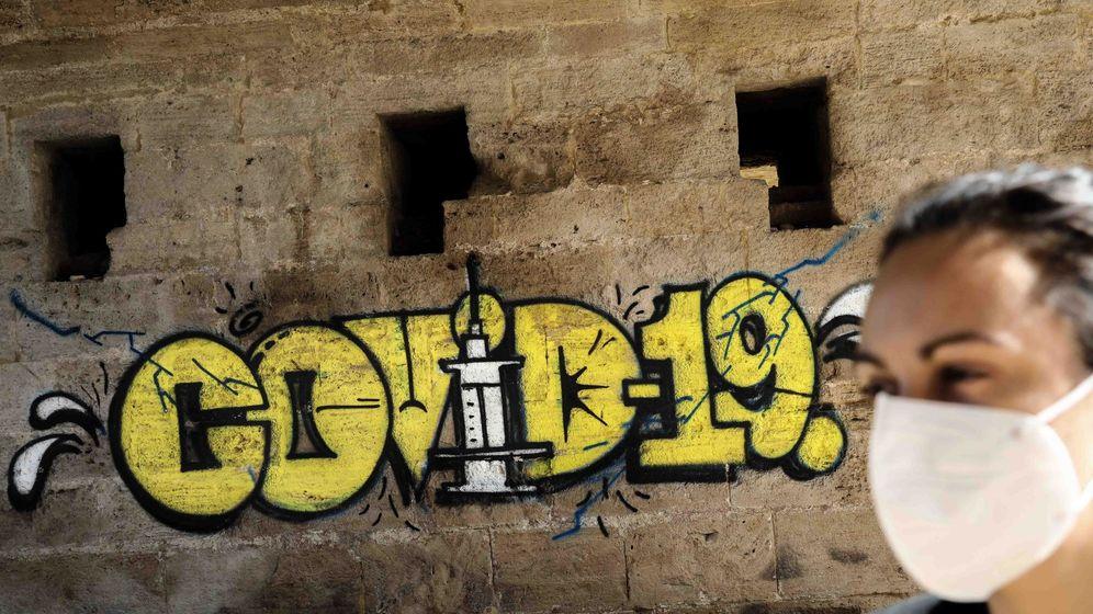 Foto: Una persona con mascarilla pasa ante un grafiti este miércoles en Valencia. (EFE)