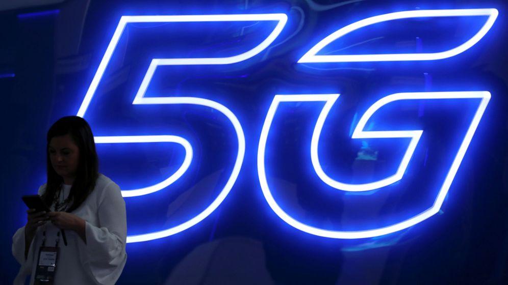 Foto: Una mujer mira su móvil frente a una representación de la red 5G. (Reuters)