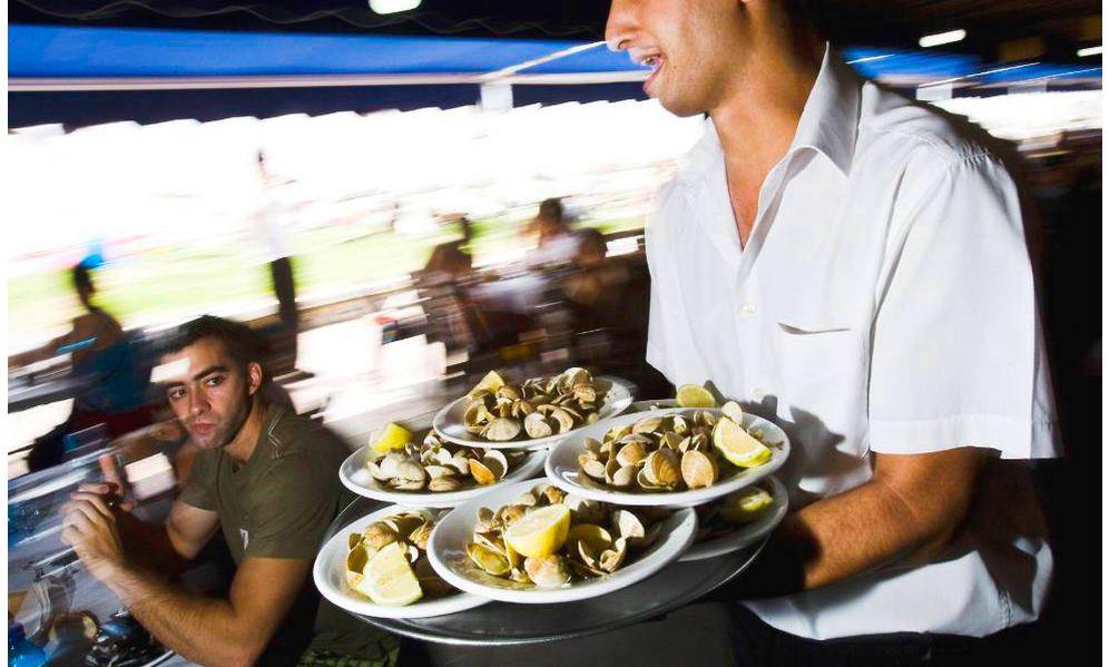 Foto: Un camarero mientras sirve varios platos en una terraza. (EFE)