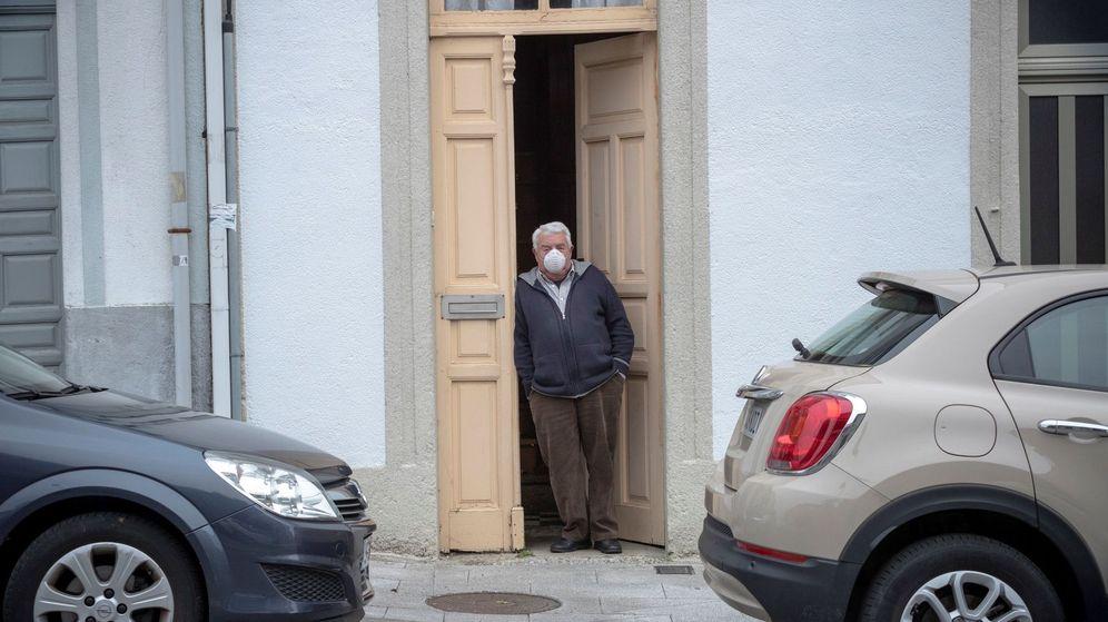 Foto: Un hombre ataviado con mascarilla se asoma a la puerta de su casa en de Palas de Rei, en Lugo, el pasado abril. (EFE)