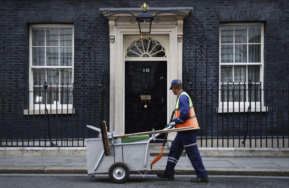 Foto: Un empleado de la limpieza pasa ante el nº 10 de Downing Street. (EFE)