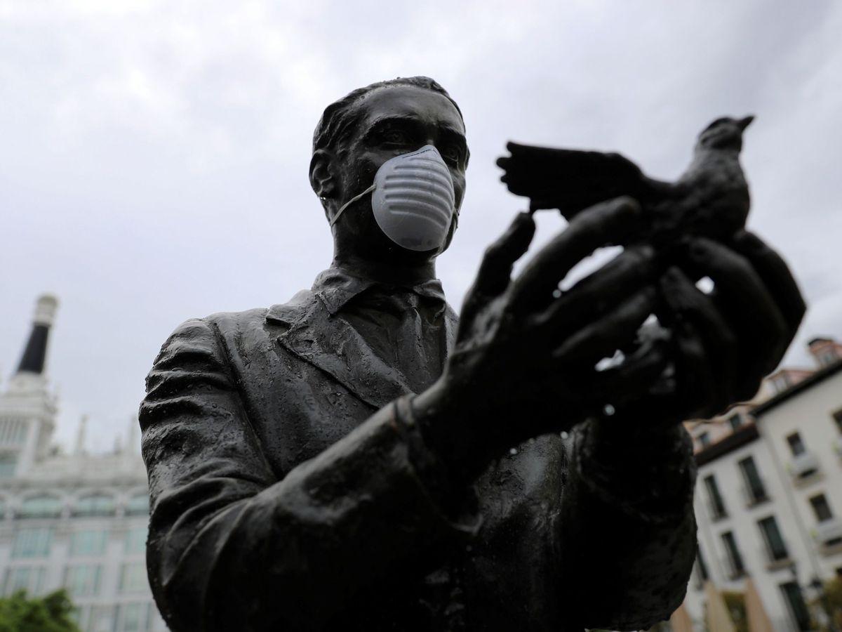 Foto: La estatua de Federico García Lorca de la plaza de Santa Ana en Madrid con mascarilla. (EFE)