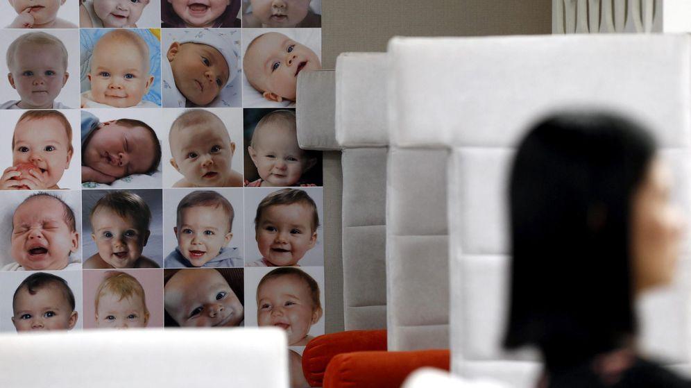 Foto: Una mujer espera a un asesor junto a decenas de retratos de bebés en una clínica de fertilidad en Bangkok. (EFE)