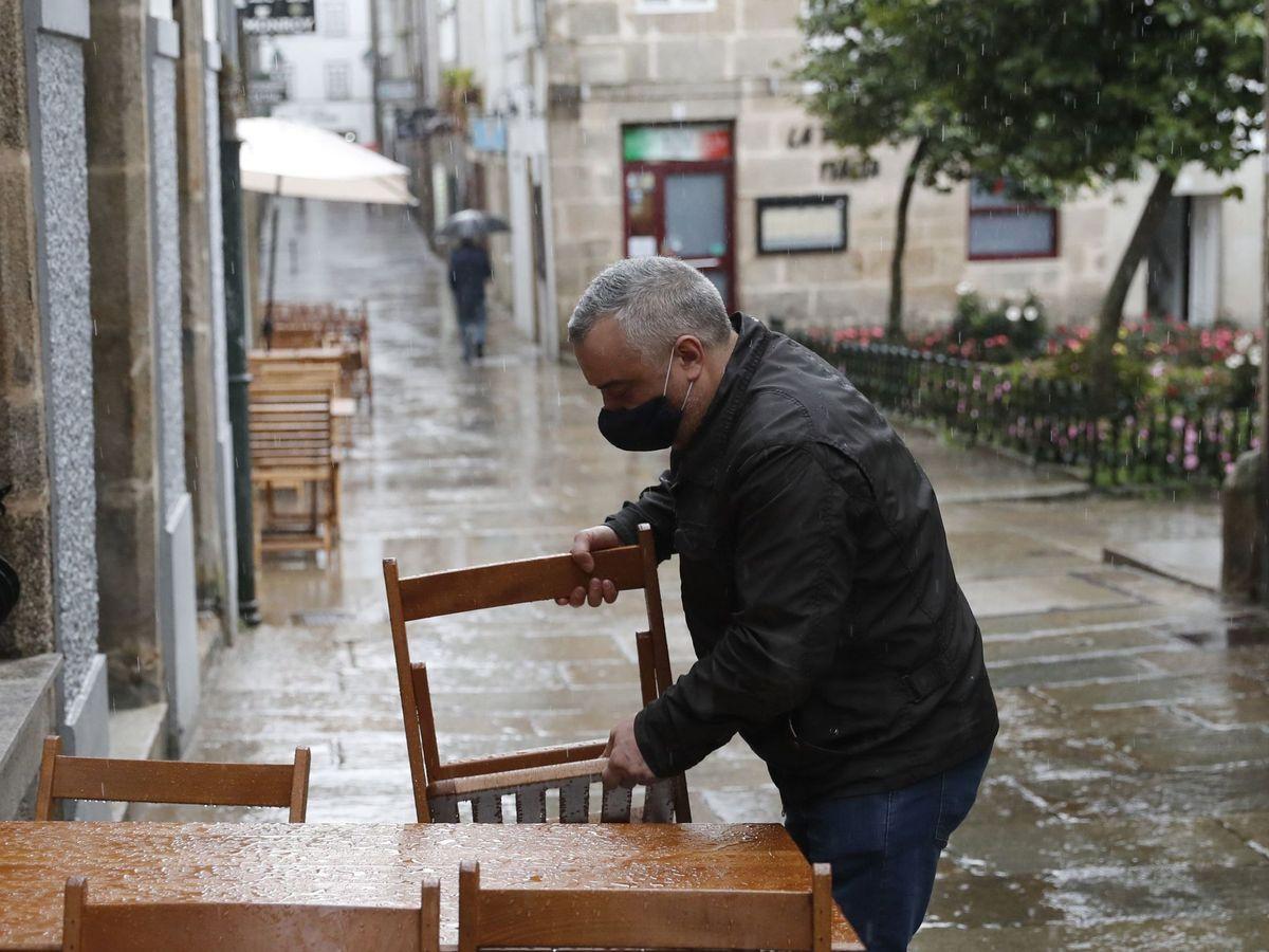 Foto: El dueño de un local de Santiago de Compostela coloca una mesa de terraza en una calle casi vacía. (EFE)