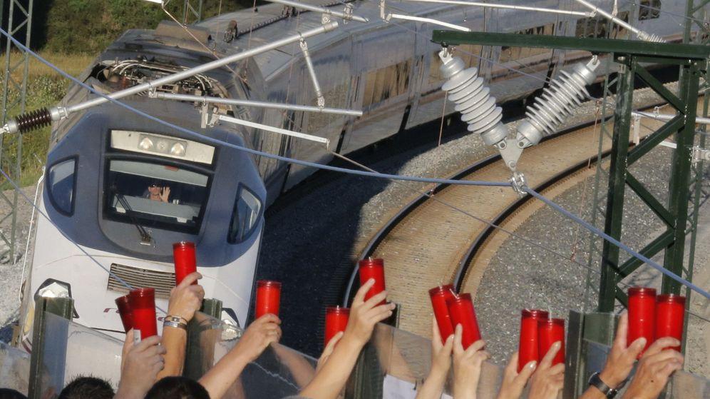 Foto: Los vecinos de Angrois alzan los cirios, mientras el conductor los saluda, al paso tren que hace la ruta del que descarriló en 2013. (EFE)