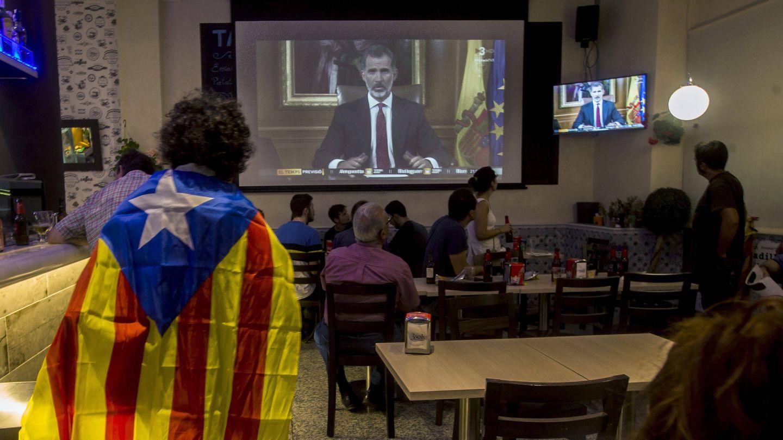 Varias personas miran el discurso del Rey tras el referéndum ilegal del 1 de octubre. (EFE)