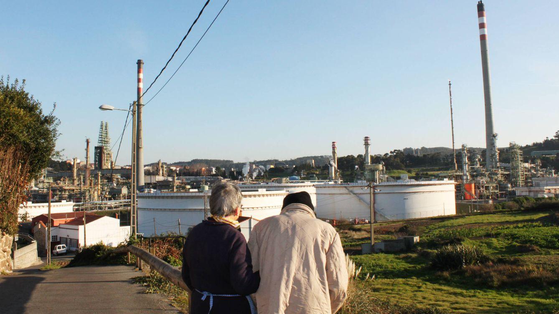 Foto: Dos personas pasean por la aldea de Nostián, en A Coruña, junto a la refinería de Repsol. (Manuel Varela)