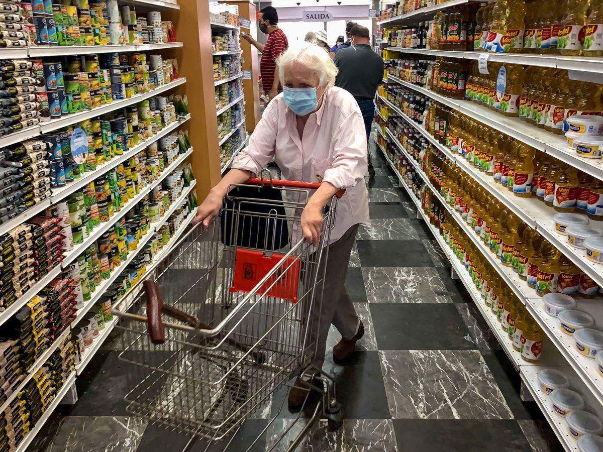 Foto: Un grupo de personas revisa precios de productos en un supermercado. (EFE)