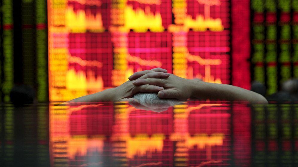 Foto: Un hombre observa una pantalla con información bursátil en Shanghái. (Reuters)