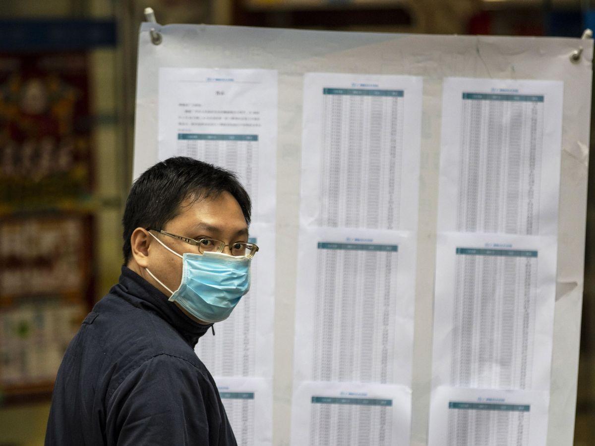 Foto: Un hombre comprueba las listas de gente agraciada con mascarillas en un sorteo organizado por el Gobierno chino a través de WeChat, el WhatsApp chino. (EFE)