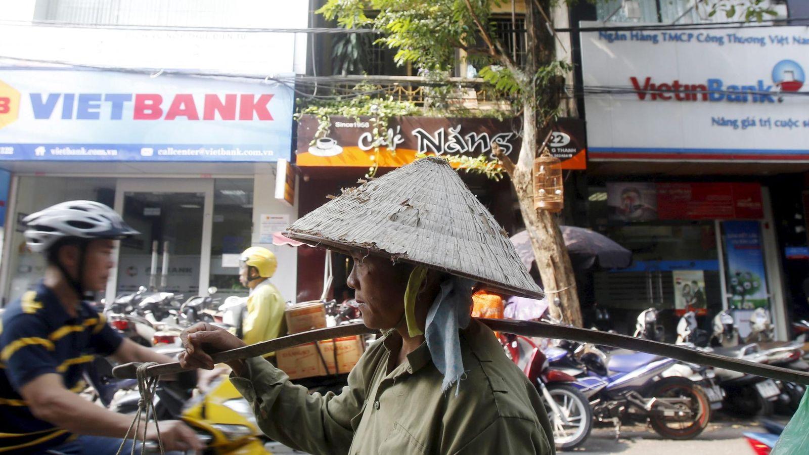 Foto: Un vendedor de frutas pasa por delante de oficinas de Vietbank y VietinBank en Hanoi, Vietnam, el 22 de octubre de 2015. (Reuters)