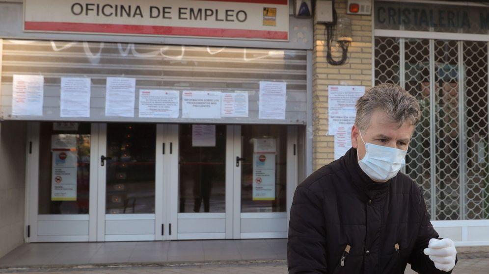 Foto: Un hombre con mascarilla y guantes pasa por delante de una oficina de empleo en Madrid (EFE)