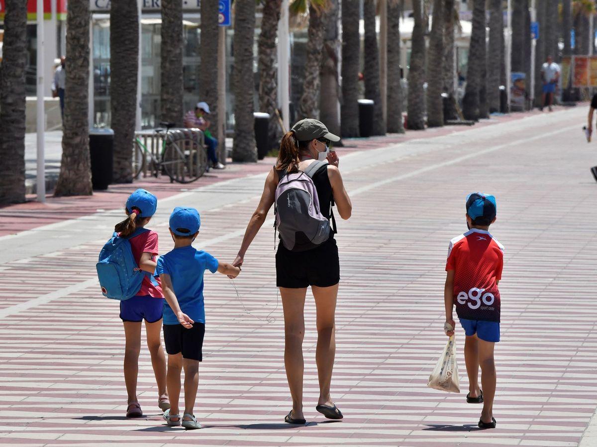 Foto: Una mujer y tres niños dan un paseo en Alarmería. (Efe)