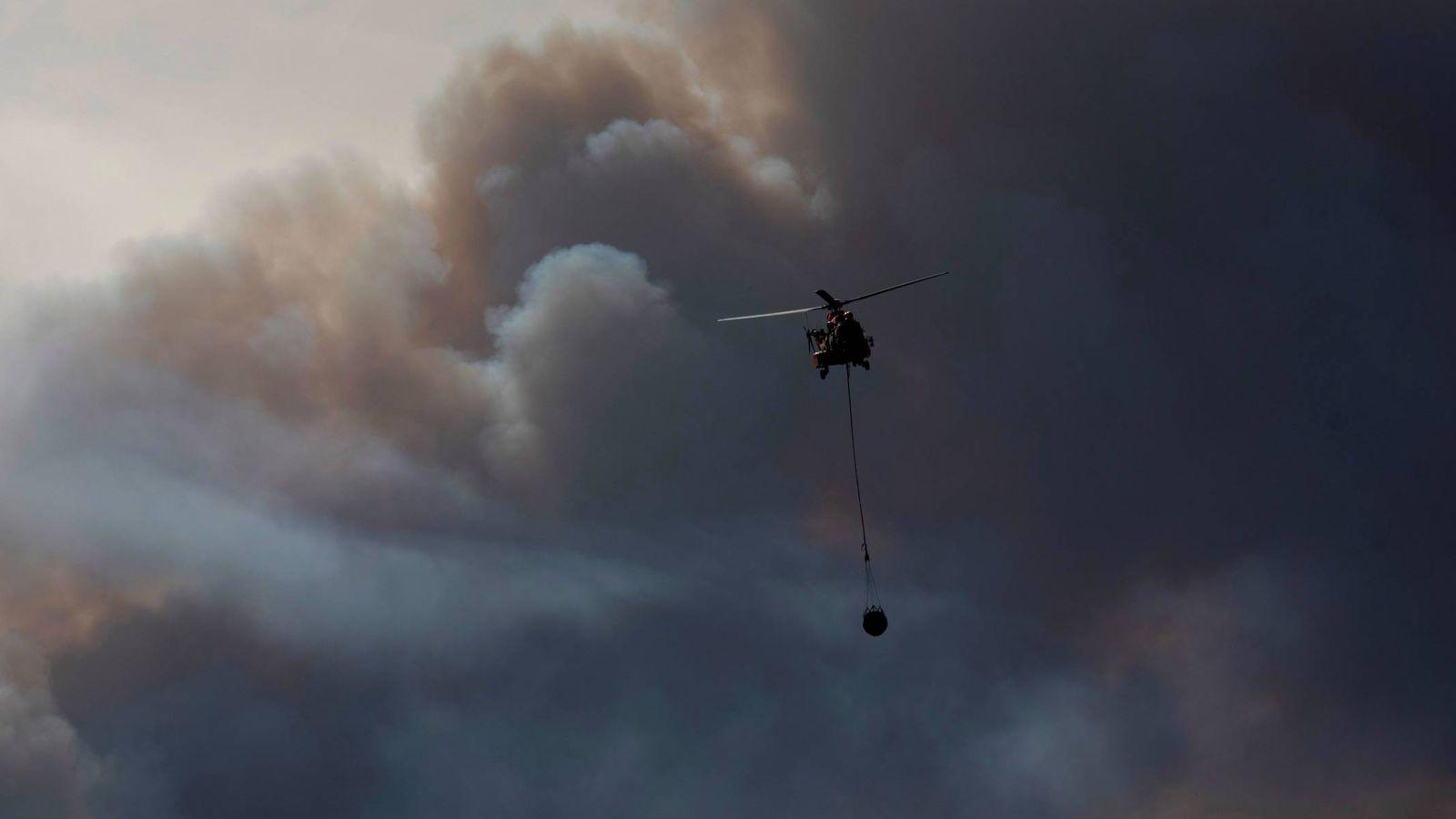 Foto: Un helicóptero en labores de extinción en las inmediaciones de la localidad de Bovera, en Tarragona. (EFE)