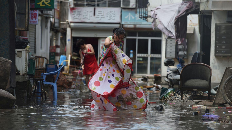 Los ciudadanos achican agua de las calles inundadas por el tifón. (Reuters)