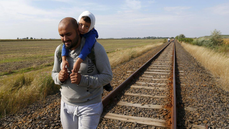 Un inmigrante recorre junto a su hijo la frontera entre Serbia y Hungría. (Reuters)