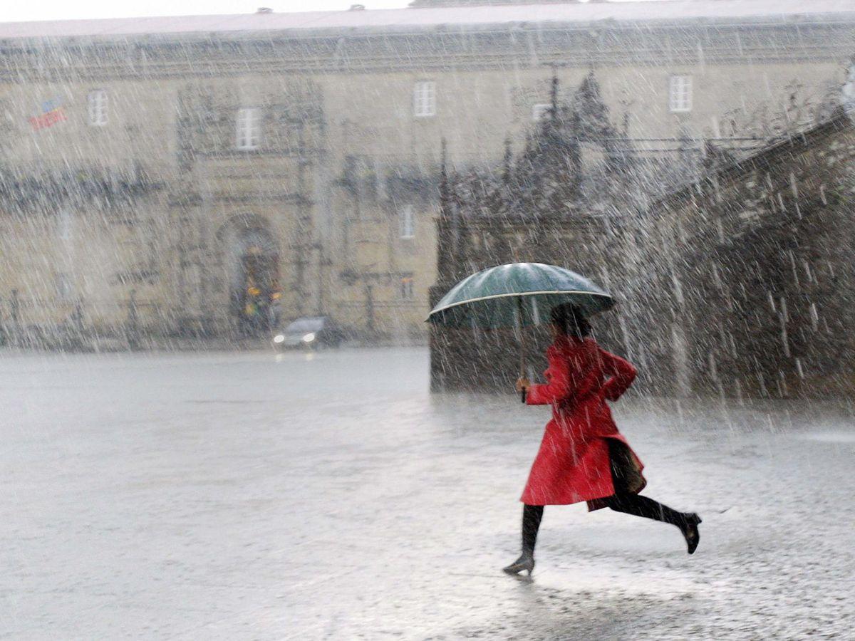Foto: Una mujer corre bajo la lluvia en Santiago de Compostela. (Efe)