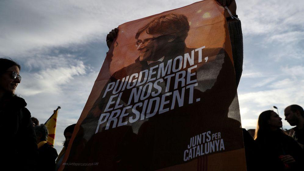 Foto: Un hombre sostiene una pancarta con la cara de Carles Puigdemont. (Reuters)