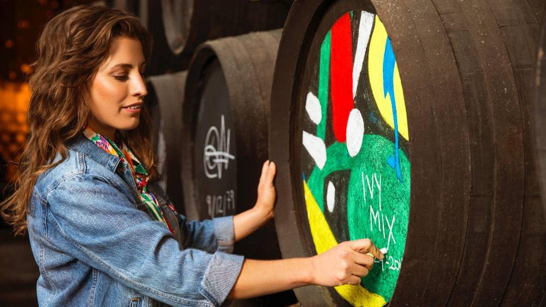 La bartender firmando una barrica cargada de color. (Cortesía)