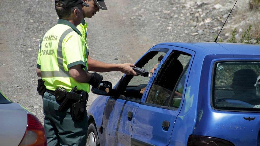 Foto: Un conductor, sometido a una prueba por varios guardias civiles. (EFE)
