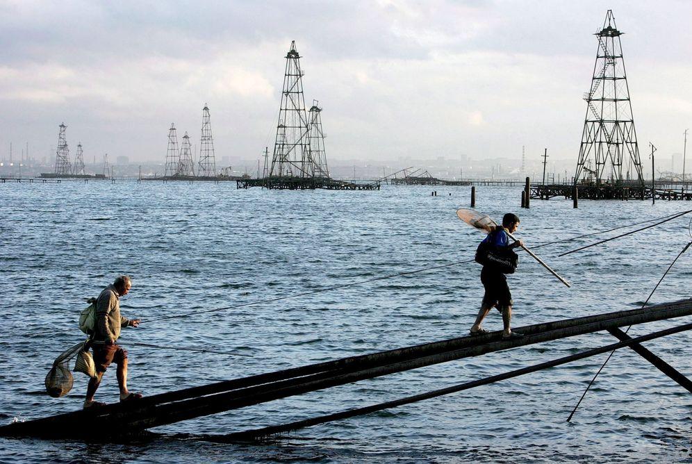 Foto: Dos trabajadores caminan frente a los pozos petrolíferos frente a las costas de Bakú, en el mar Caspio. (EFE)