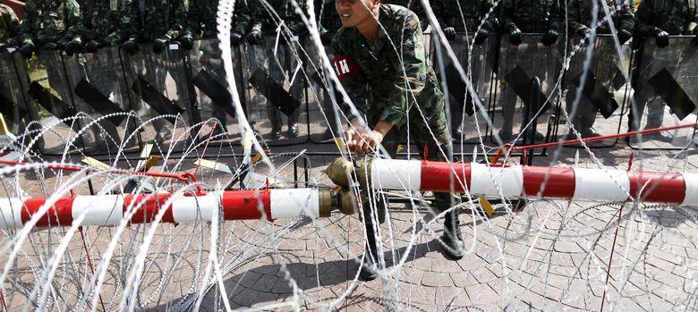 Foto: Un oficial ajusta la alambrada colocada para contener las protestas antigubernamentales ante el Ministerio de Defensa en Bangkok. (Reuters)