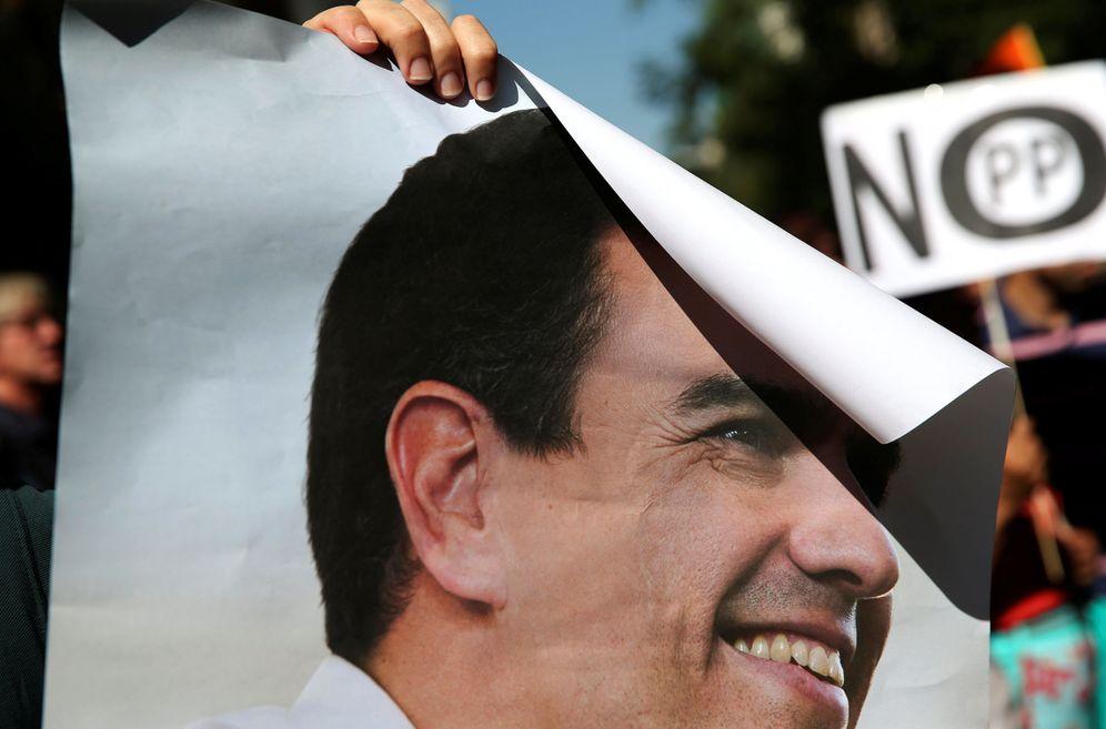 Foto: Un manifestante sostiene un cartel de Pedro Sánchez y otro uno de 'No al PP', el pasado 1 de octubre en Ferraz, mientras se celebraba el comité federal del PSOE. (Reuters)