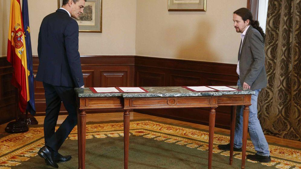 Foto: El presidente del Gobierno en funciones, Pedro Sánchez, y el líder de Podemos, Pablo Iglesias, antes de la firma del preacuerdo para el Gobierno de coalición. (EFE)