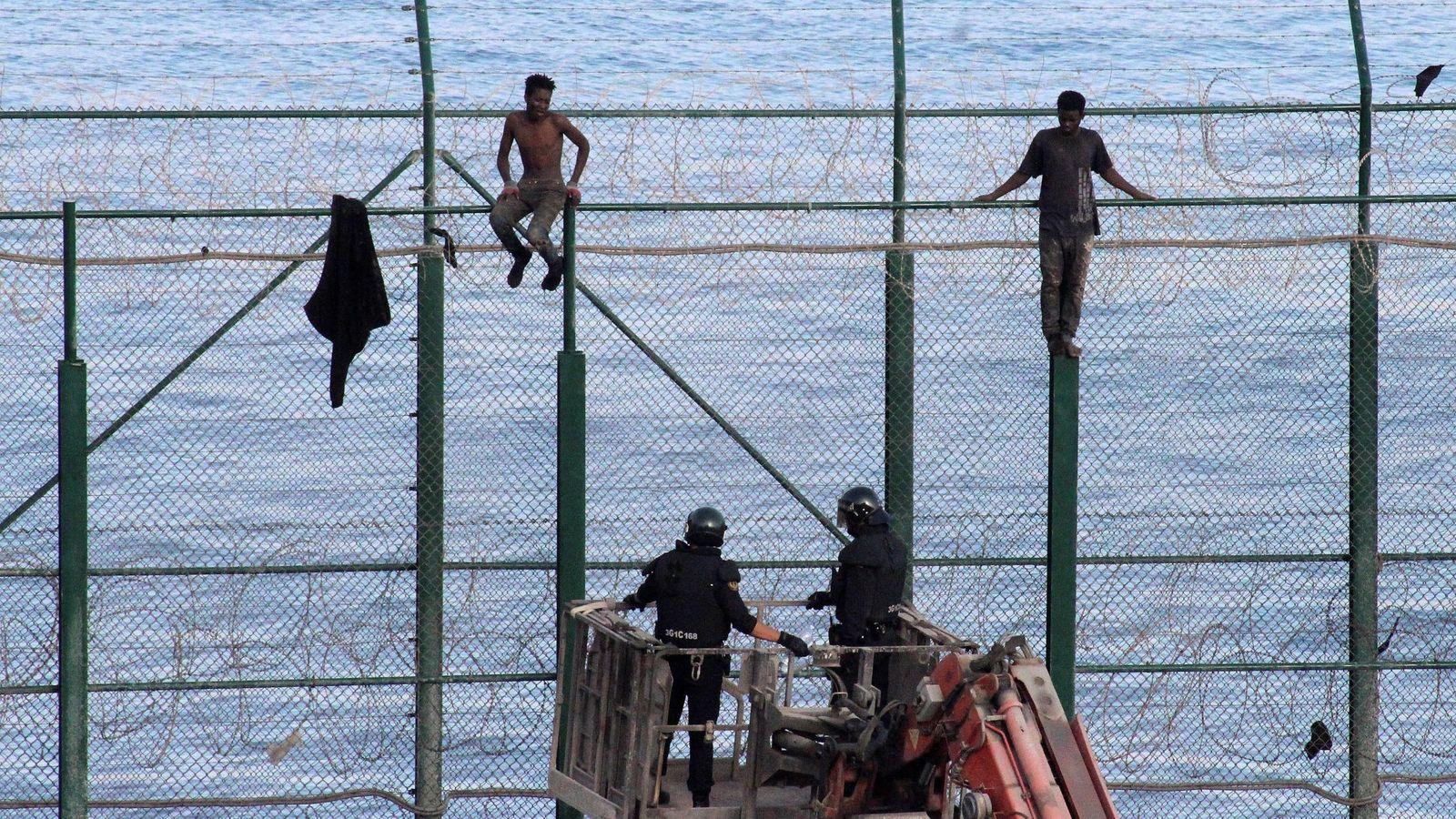 Foto: Foto de archivo de dos migrantes subsaharianos en la valla fronteriza de Ceuta con Marruecos vigilados por la Policía. (EFE)