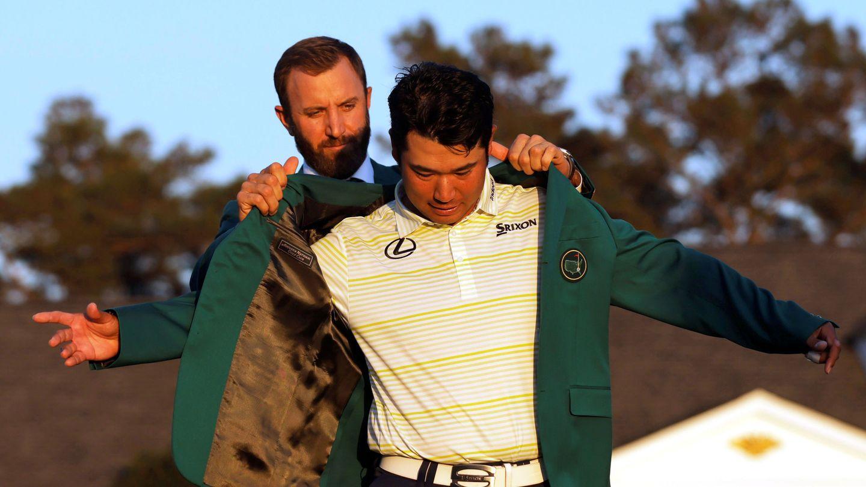 Dustin Johnson pone al japonés Hideki Matsuyama la chaqueta verde de campeón del Masters 2021. (REUTERS)
