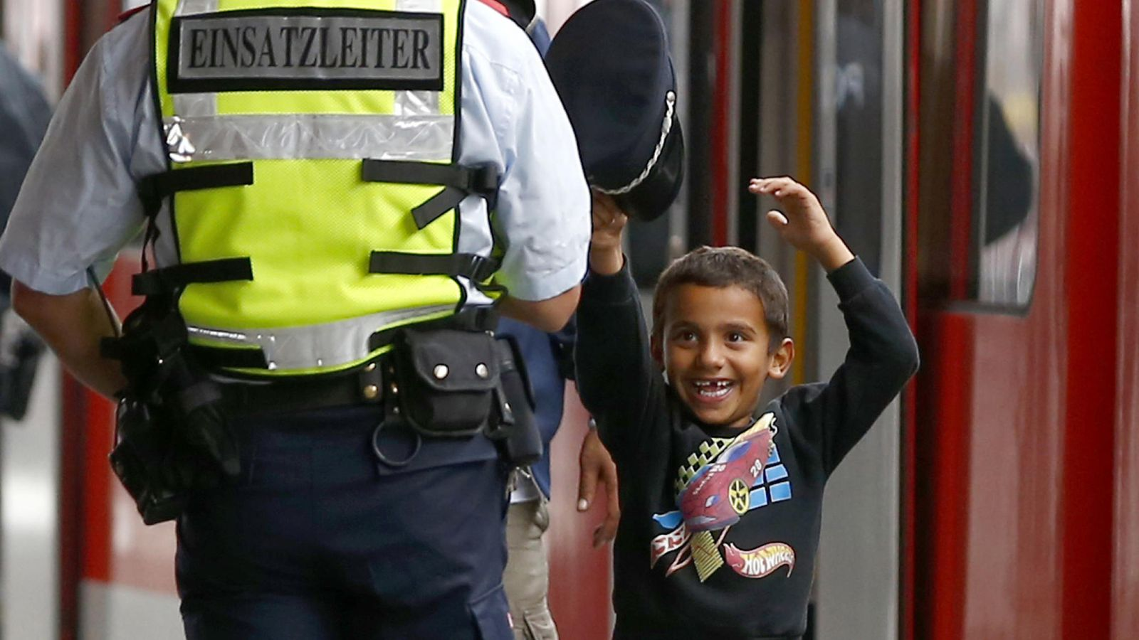Foto: Un niño refugiado juega con la gorra de un policía austriaco (Reuters).