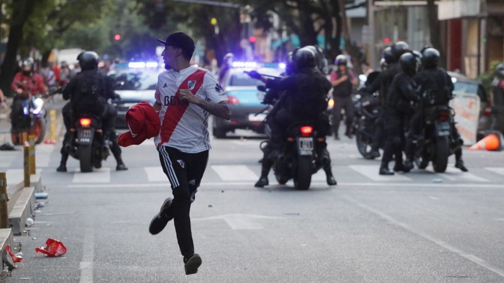 Foto: Un aficionado de River Plate corre frente a policías. (Reuters)