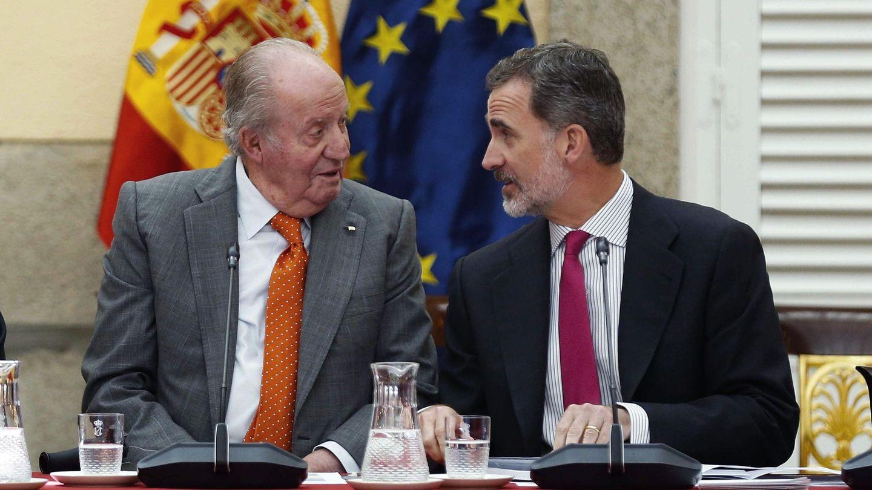 El rey Juan Carlos y el rey Felipe conversan en un acto. (EFE)