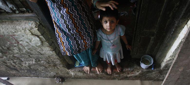 Foto: Una niña observa al fotógrafo desde el umbral de su casa en Nueva Delhi (Reuters).