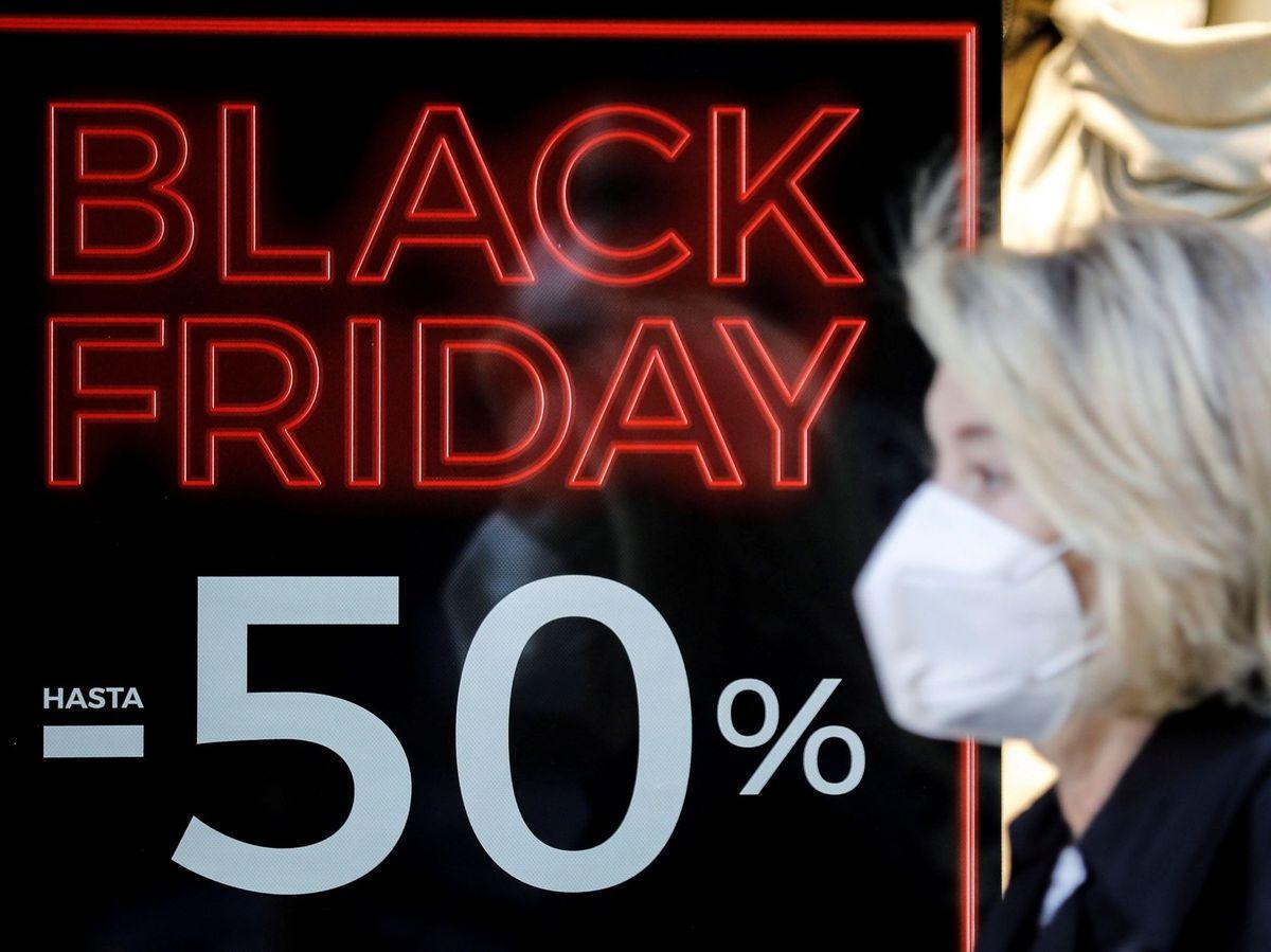 Foto: Una mujer con mascarilla pasea ante el escaparate de un comercio con promociones del Black Friday (EFE)