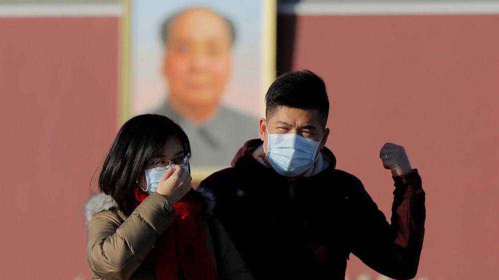 Foto: Una pareja camina por el centro de Pekín con mascarillas. (EFE)