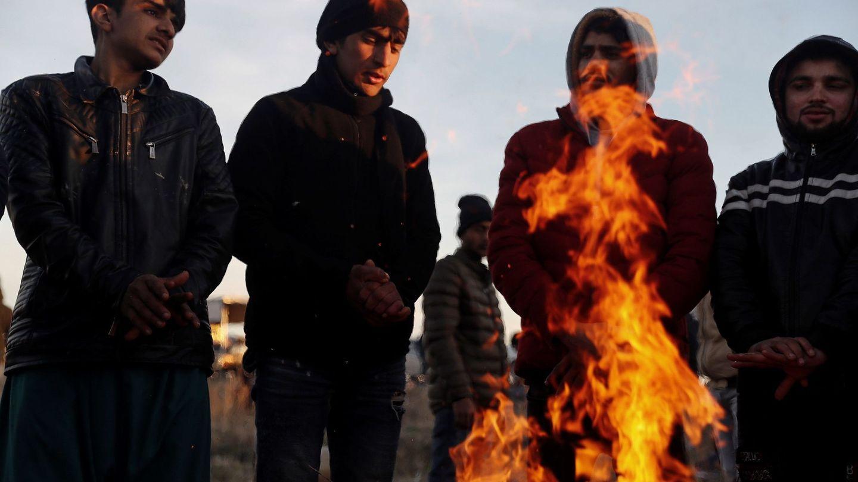 Varios refugiados se calientan junto a una hoguera en Ipsala (Turquía). (EFE)