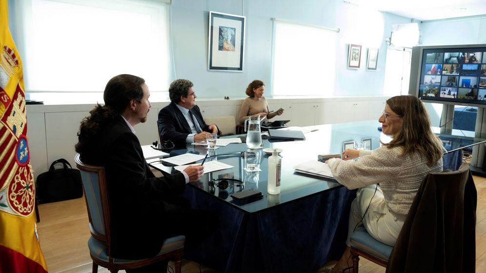 Foto: El vicepresidente segundo, Pablo Iglesias (i), junto a la ministra de Trabajo, Yolanda Díaz (d), y el de Seguridad Social, José Luis Escrivá (c), en videoconferencia con los titulares de Trabajo de la UE. (EFE)