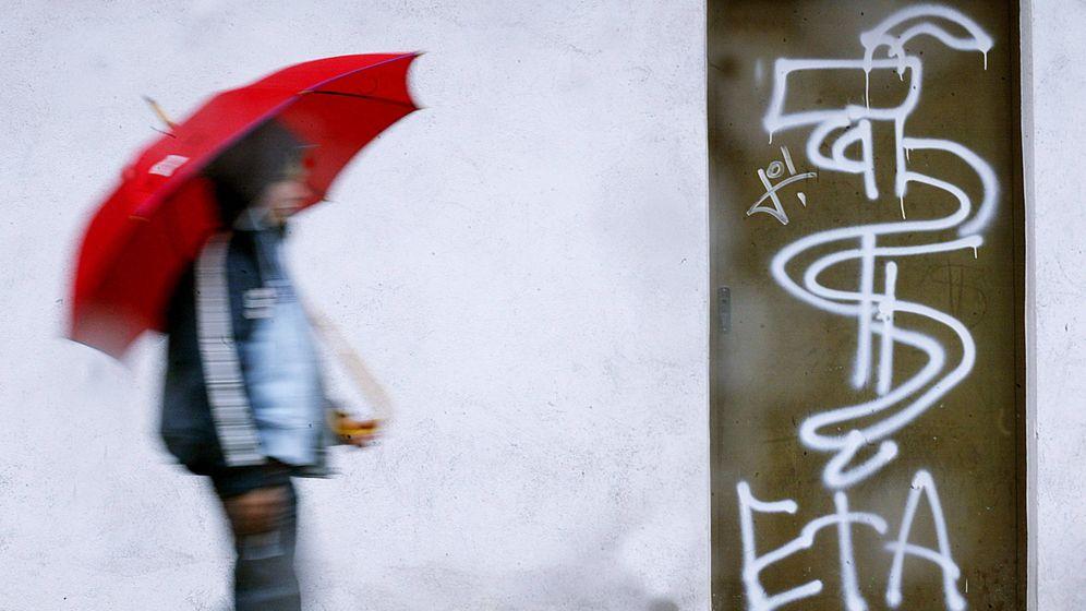 Foto: Un joven pasa junto a una pintada de ETA en la ciudad de Guernica. (Reuters)