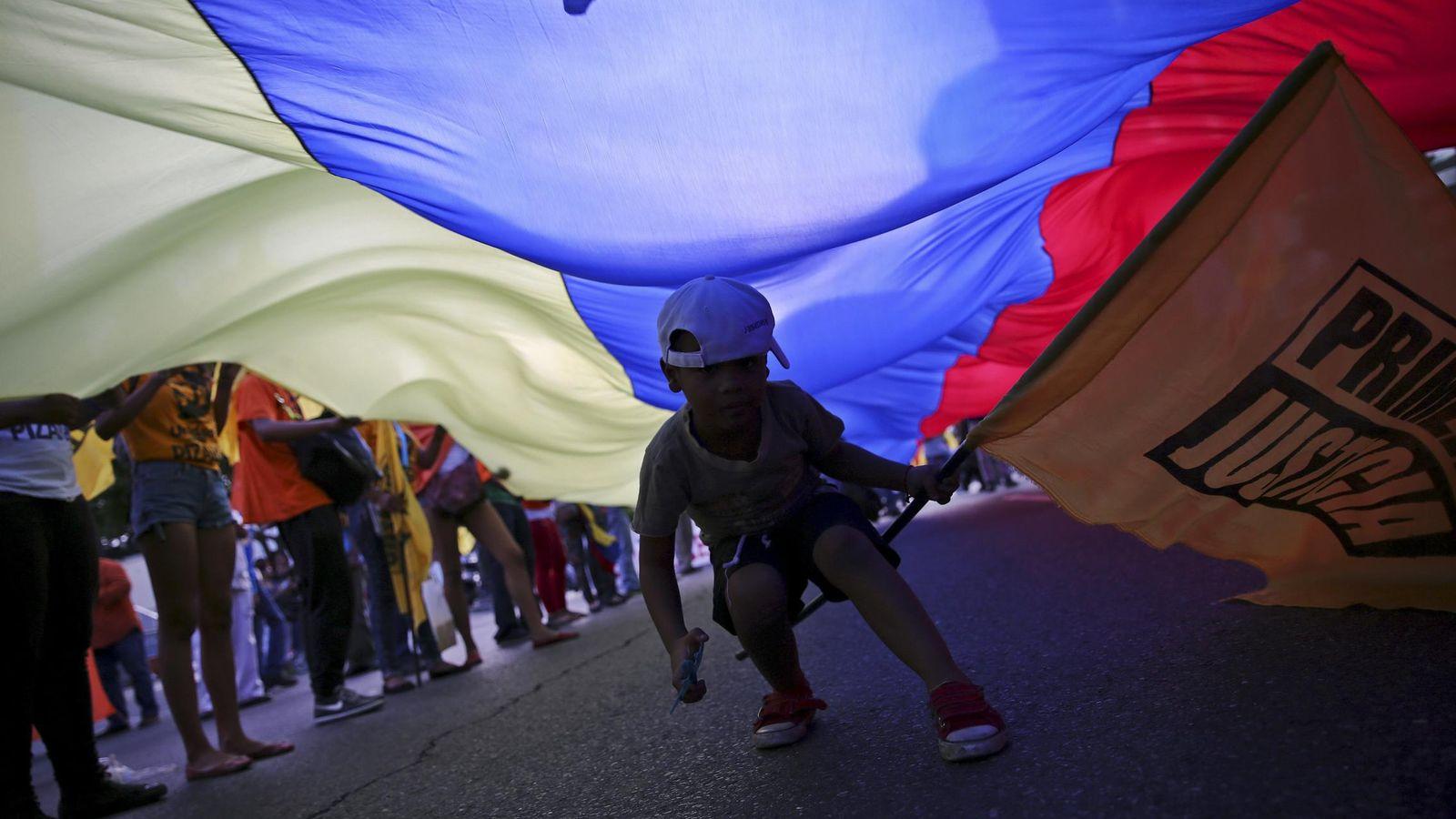 Foto: El hijo de un opositor sostiene una bandera donde puede leerse 'Justicia', durante un mitin electoral de la oposición venezolana, en Caracas, el 3 de diciembre de 2015 (Reuters).