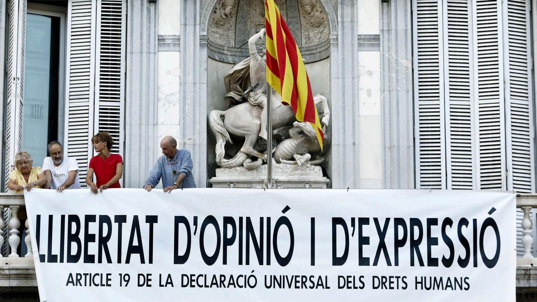 Lluís Llach (d), Antonio Baños (2i) y Silvia Bel (3i) colocan una pancarta en la sede de la Generalitat. (EFE)