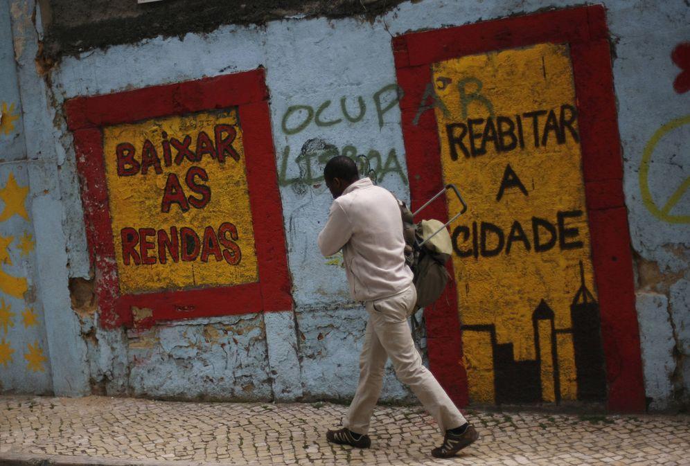 Foto: Un hombre pasa ante una pintada que pone alquileres más bajos, en Lisboa. (Reuters)