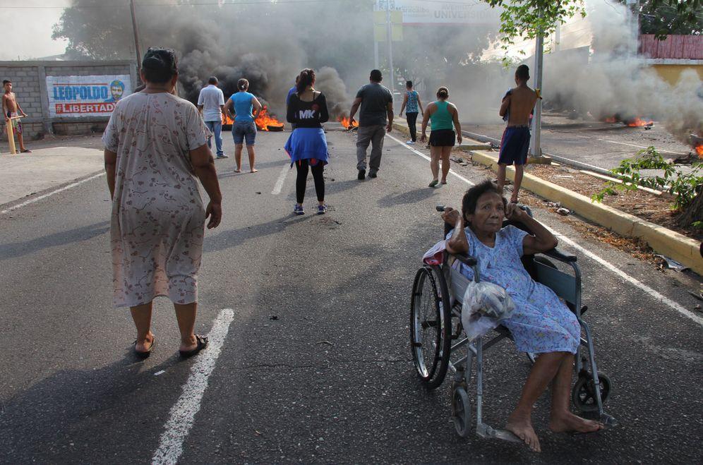 Foto: Un grupo de personas observa un corte de carretera durante una protesta por los cortes de energía en Maracaibo, Venezuela, el 26 de abril de 2016 (EFE)