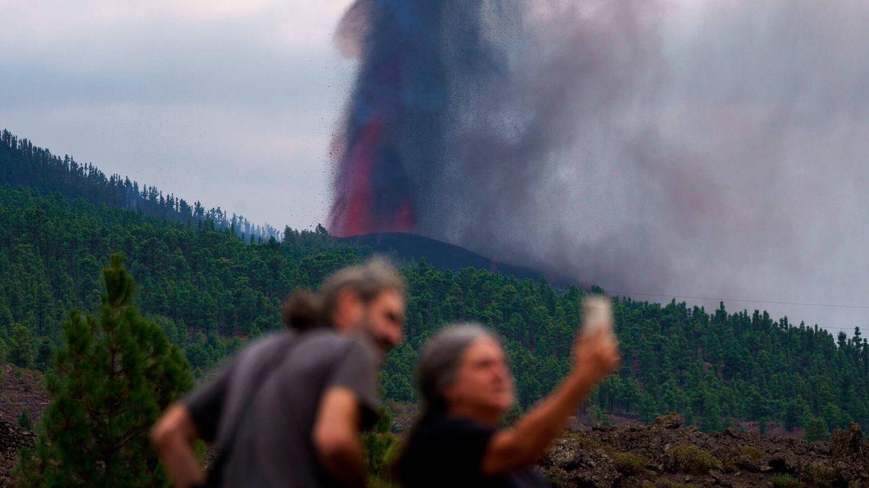Foto: Dos personas observan la actividad de la erupción volcánica. (EFE)